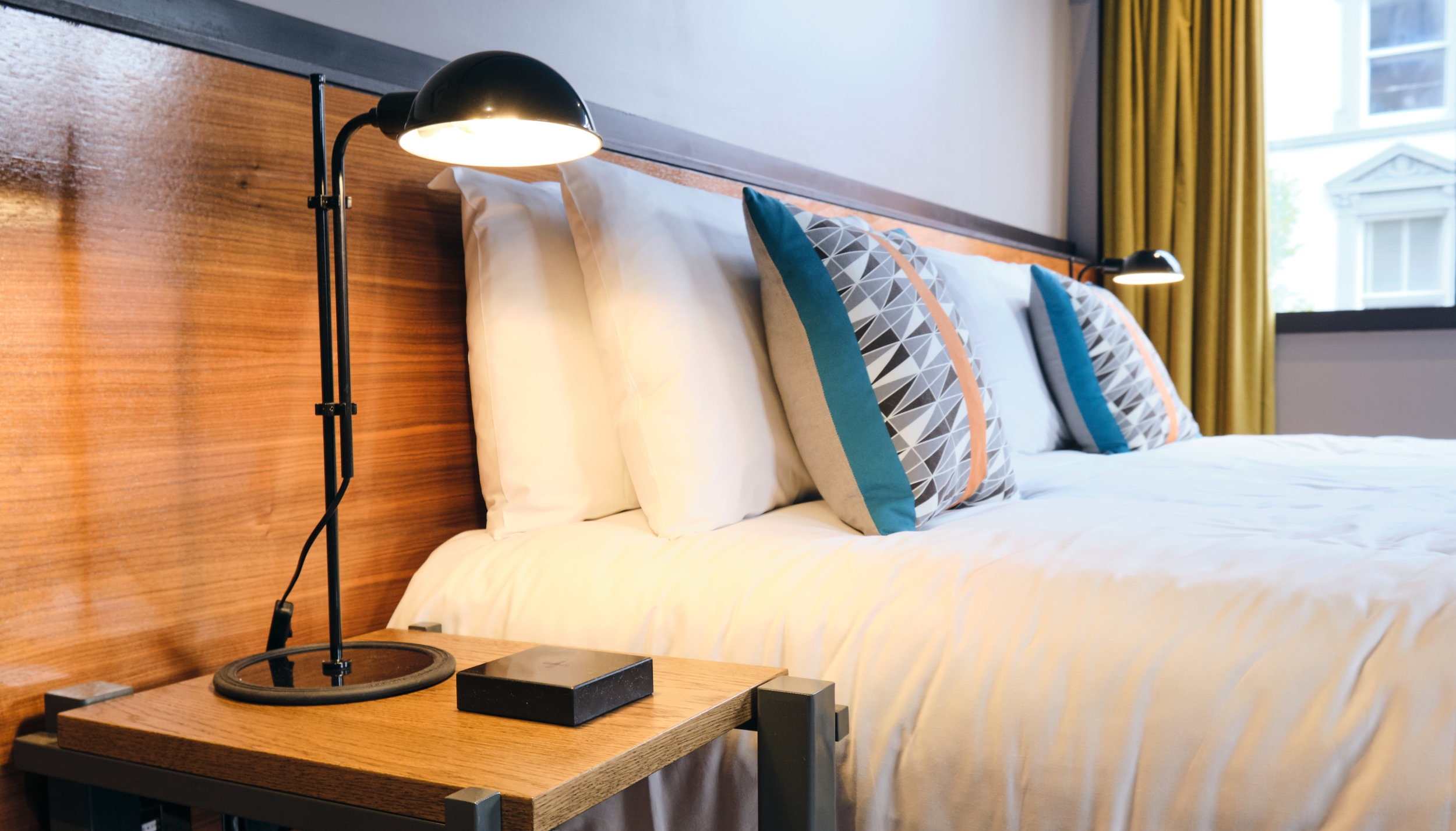 double bed in hotel room with Chargifi SmartSpot on bedside table
