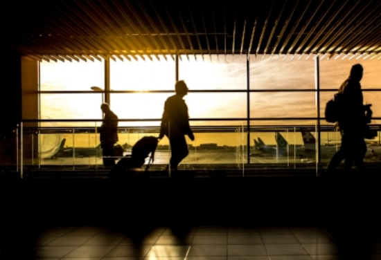 Silhouetted figures walking through an airport at sunset