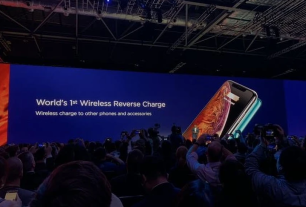 Image of world's first wireless reverse charge phone on a big screen at conference